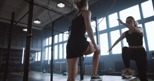 Two young beautiful athletic caucasian women, coach and trainee, working out exercising together in gym slow motion. Female athletes do aerobics training in stock footage