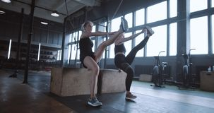 Two young beautiful athletic Caucasian women exercising together in large gym. Personal coach workout plan slow motion. Female athletes do aerobics training in stock video footage