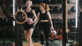 Two young beautiful athletic Caucasian women walk along gym with kettlebell weights talking casually slow motion. Active lifestyle and extreme sports, female stock footage