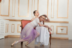 Two young beautiful ballet dancers sitting on sofa Royalty Free Stock Photo