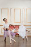 Two young beautiful ballet dancers sitting on sofa Stock Photos