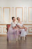 Two young beautiful ballet dancers sitting on sofa Stock Images