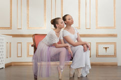 Two young beautiful ballet dancers sitting on sofa Royalty Free Stock Image