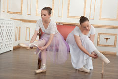Two young beautiful ballet dancers sitting on sofa Royalty Free Stock Photos