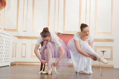 Two young beautiful ballet dancers sitting on sofa Stock Image