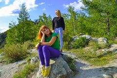 Two young beautiful blonde girls and redhead on a rock on a sunny warm autumnal summer day resting while traveling near a green t stock images