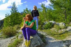 Two young beautiful blonde women and redhead on a rock on a sunny warm autumnal summer day resting while traveling near a green t stock images