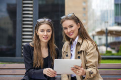 Two young beautiful business women sitting on a bench Stock Photography