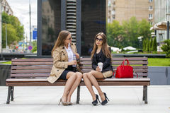 Two young beautiful business women sitting on a bench Royalty Free Stock Photography