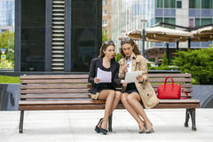 Two young beautiful business women sitting on a bench Royalty Free Stock Photos
