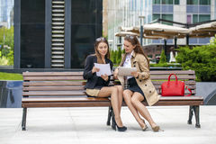 Two young beautiful business women sitting on a bench Royalty Free Stock Image