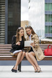 Two young beautiful business women sitting on a bench Stock Photo