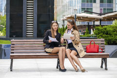 Two young beautiful business women sitting on a bench Stock Images