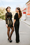 Two young beautiful fashionable woman in black clothes posing for the photographer. Headbands on the head, in the ears Royalty Free Stock Photo