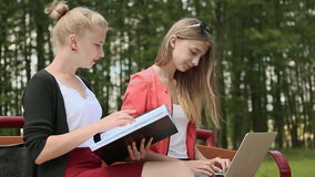 Two young beautiful female student with laptop in hand on a bench in green park. Study. Discussion. Side view. stock footage