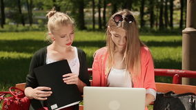 Two young beautiful female student with laptop in hand on a bench in green park. Study. Front view. stock footage