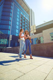 Two young beautiful females walking along the street and chattin Royalty Free Stock Photo