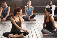 Two young beautiful fit women talking at group yoga training stock image