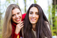 Two young beautiful girl enjoying the sunny autumn day Royalty Free Stock Image