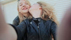 Two young beautiful girlfriends blonde fun and coquettish posing in front of the camera. Do selfie. Spring. stock footage