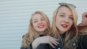 Two young beautiful girlfriends blonde fun and coquettish posing in front of the camera. Do selfie. Spring stock footage