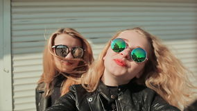 Two young beautiful girlfriends blonde in sun glasses on her face fun and coquettish posing in front of the camera. Do. Selfie. Spring stock video