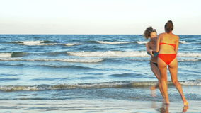 Two young beautiful girlfriends playing in the water on the beach stock footage