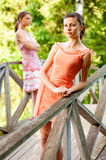 Two young and beautiful girls at banisters. Of little bridge in city-park royalty free stock image