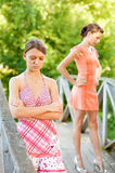 Two young and beautiful girls at banisters. Of little bridge in city-park stock images