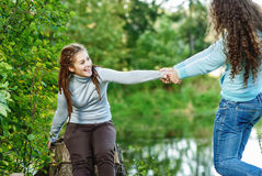 Two young and beautiful girls at banisters. Of little bridge in city-park royalty free stock images
