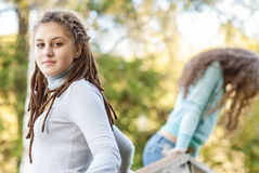 Two young and beautiful girls at banisters. Of little bridge in city-park royalty free stock photo