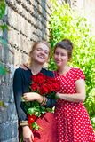 Two young and beautiful girls, with a bouquet of red roses stand on the background of an old brick wall. royalty free stock photography