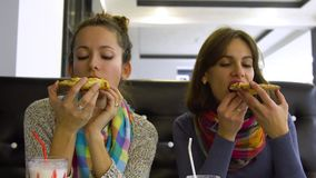 Two young beautiful girls in a cafe drink cocktails and eat pizza. They are happy and have fun. 4K stock video