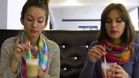 Two young beautiful girls in a cafe drink cocktails and eat pizza. They are happy and have fun. 4K stock video footage