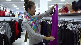 Two young beautiful girls choose clothes in a fashionable boutique. Girls carefully look at the clothes and examine it. 4K stock video