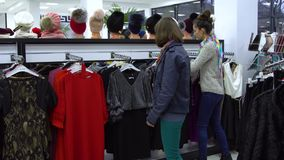 Two young beautiful girls choose clothes in a fashionable boutique. Girls carefully look at the clothes and examine it. 4K stock footage
