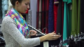 Two young beautiful girls choose clothes in a fashionable boutique. Girls carefully look at the clothes and examine it. Girls choose pants. 4K stock footage