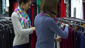 Two young beautiful girls choose clothes in a fashionable boutique. Girls carefully look at the clothes and examine it. Girls choose pants. 4K stock video