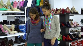 Two young beautiful girls choose shoes in a fashion boutique. The girls look attentively at the shoes and examine it. 4K stock video footage