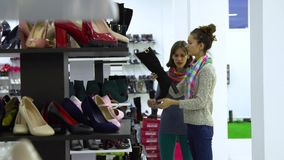 Two young beautiful girls choose shoes in a fashion boutique. The girls look attentively at the shoes and examine it. 4K stock footage