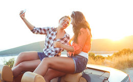 Two young beautiful girls are doing a photo of yourself in a cab Royalty Free Stock Photos
