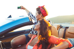 Two young beautiful girls are doing selfie in a convertible stock photography