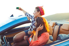Two young beautiful girls are doing selfie in a convertible stock image