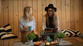 Two young beautiful girls drinking tea and read magazine stock video footage