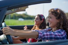 Two young beautiful girls driving in a convertible. While smiling royalty free stock photography