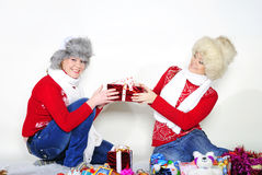Two young beautiful girls with gifts. On a white background Royalty Free Stock Photos