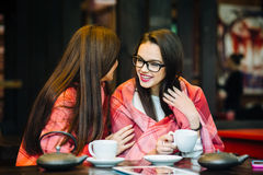 Two young and beautiful girls gossiping Royalty Free Stock Photos