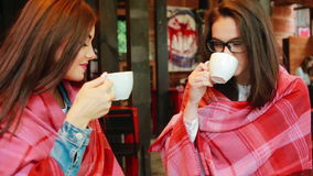 Two young and beautiful girls gossiping. On the terrace with a cup of coffee stock video footage