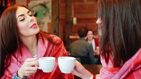 Two young and beautiful girls gossiping. On the terrace with a cup of coffee stock video