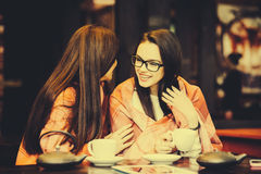 Two young and beautiful girls gossiping. On the terrace with a cup of coffee,  instagram tone Stock Images